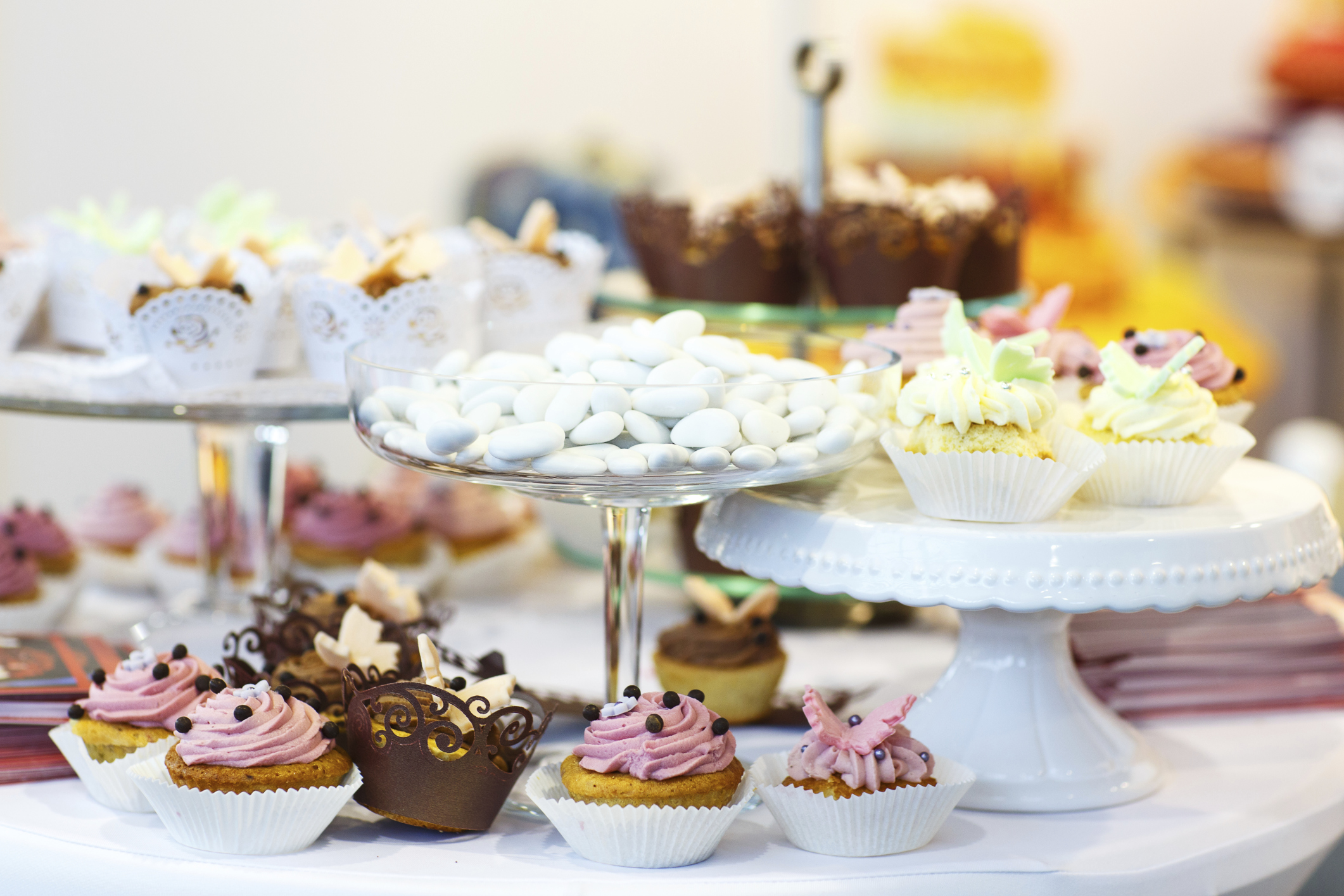Elegant sweet table with big cake, cupcakes on dinner